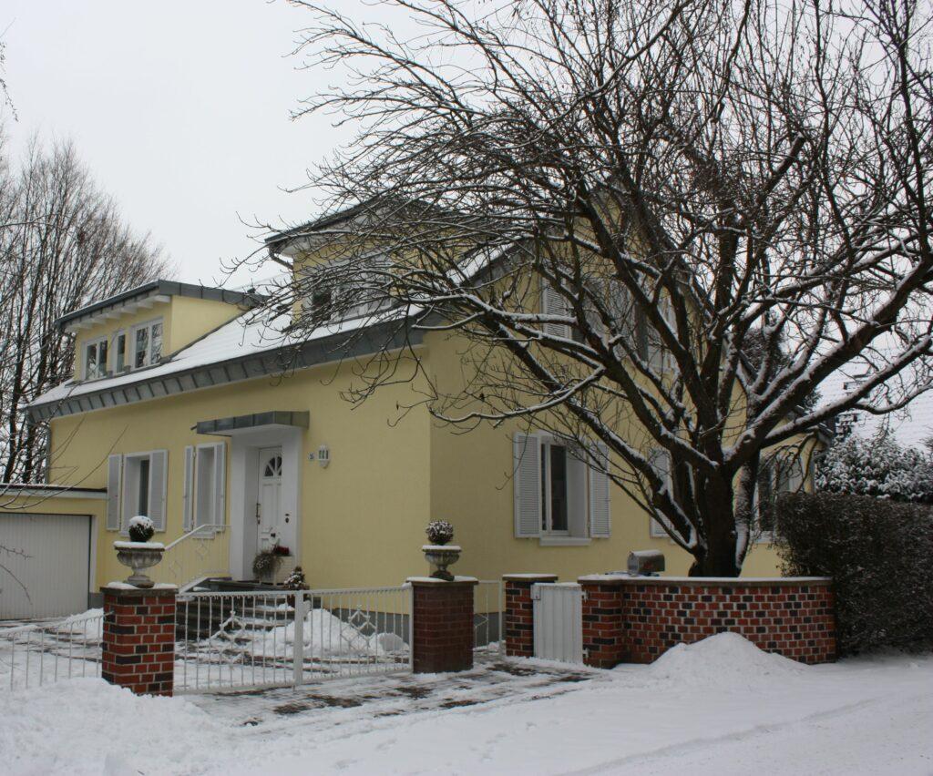 Gelbes Einfamilienhaus mit zwei Gauben in Winterlandschaft